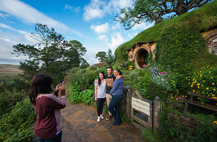 Visitors taking pictures in front of Hobbit hole in Hobbiton