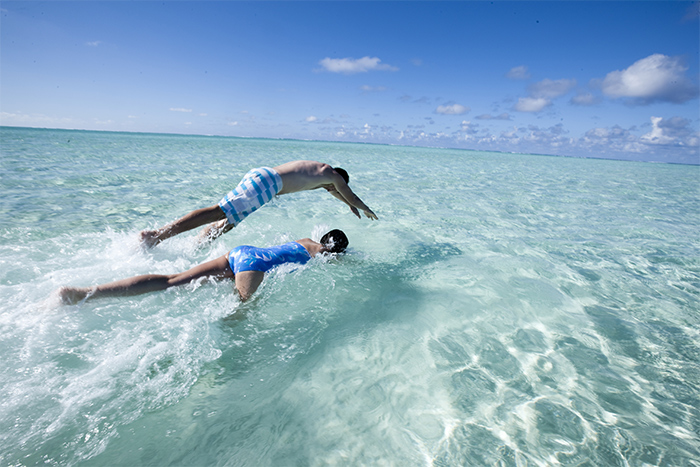Couple diving into the lagoon